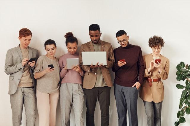 Ľudia s počítačmi, tabletmi a mobilmi v rukách stoja vedľa seba pri stene