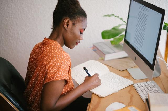 Žena v oranžovej blúzke, s výrazným mejkapom sedí v kancelárii a pracuje
