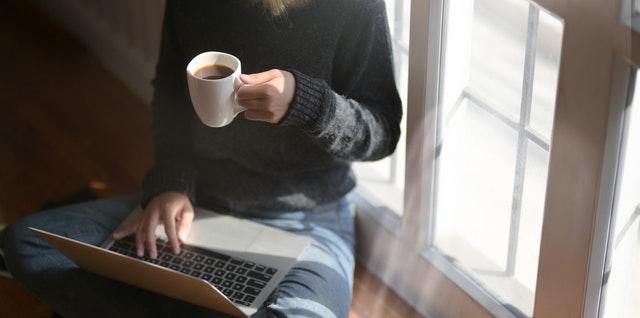 Žena s kávou v ruke píše na notebooku